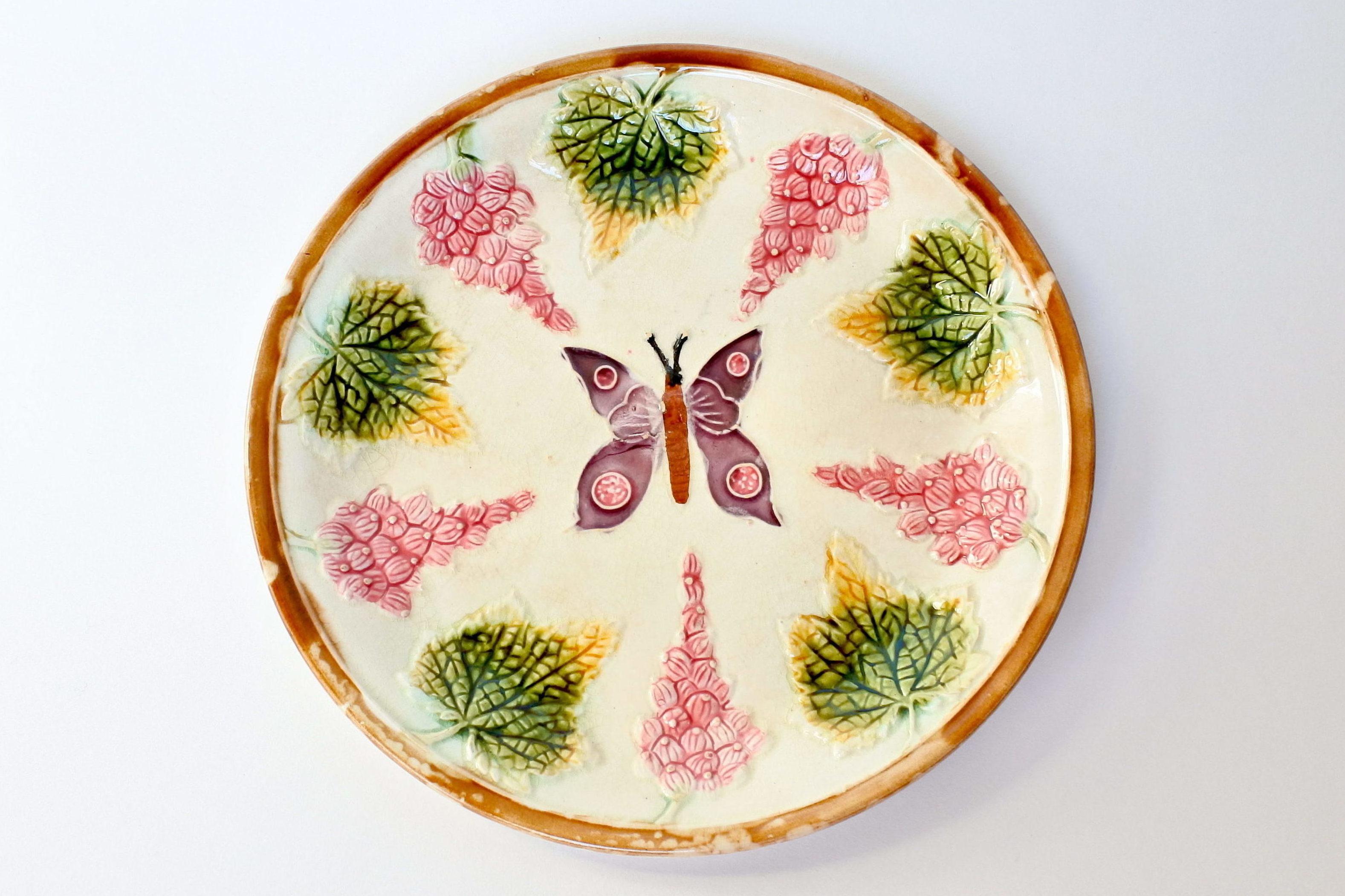 Piatto in ceramica barbotine con uva spina e farfalla