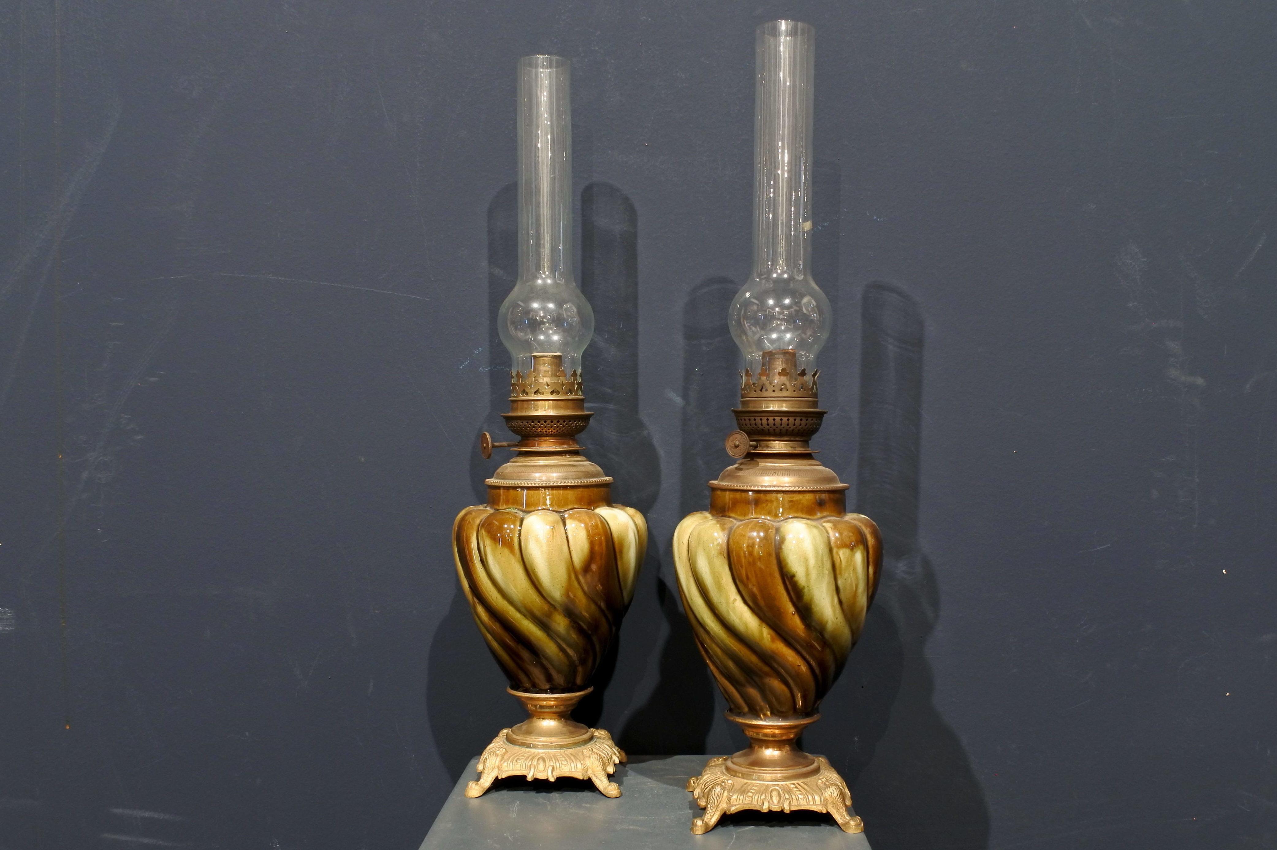 Coppia di lumi a petrolio in ceramica e bronzo