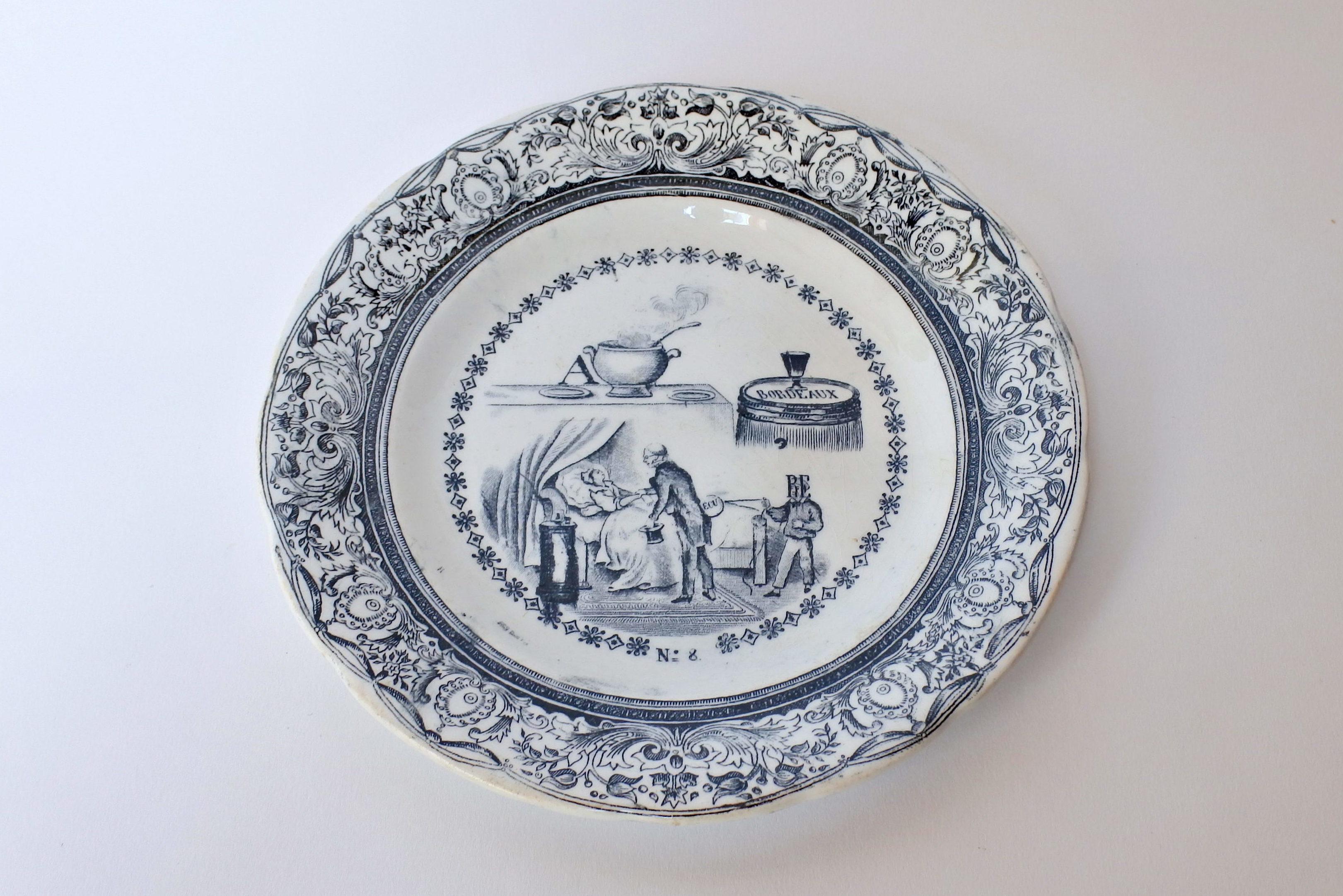 Piatto in ceramica con cornice blu e decorato con rebus