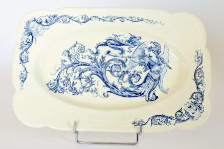 Piatto rettangolare in ceramica di Clairefontaine con angelo grottesche e volute