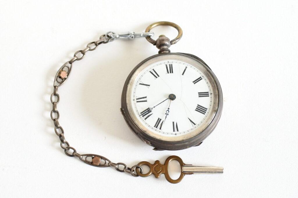 Orologio da tasca in argento con cassa incisa e catena con chiavetta di carica