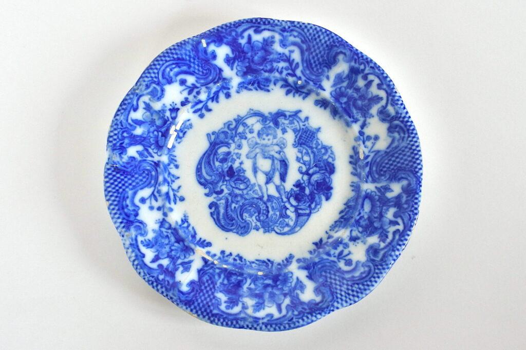 Piatto antico in ceramica con putto che suona il flauto di Pan