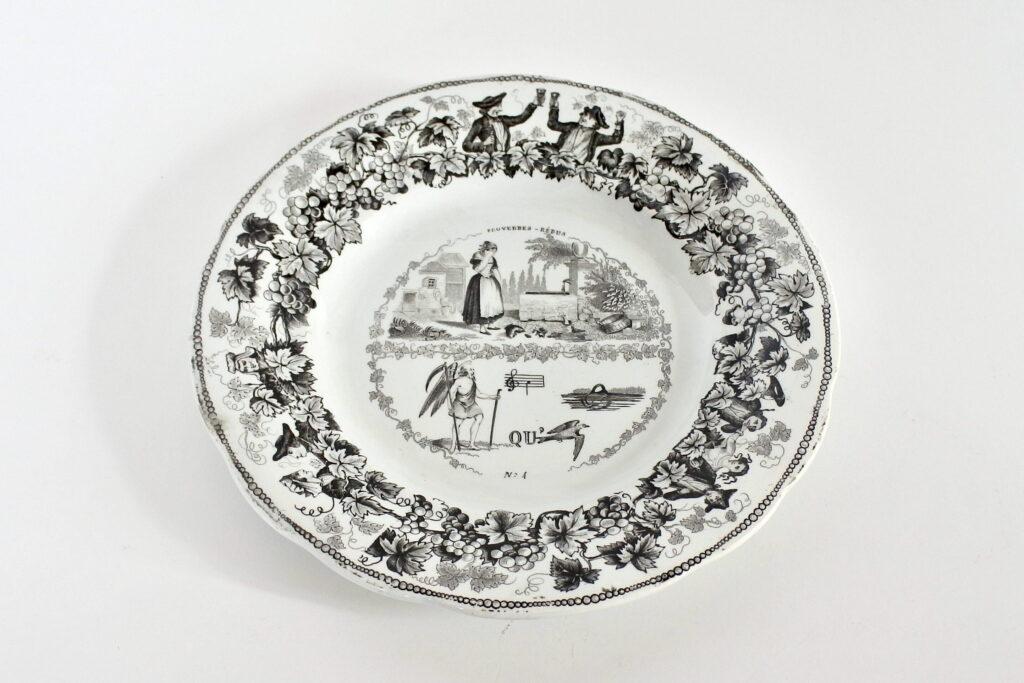 Piatto in ceramica con rebus e bordo monocromatico nero