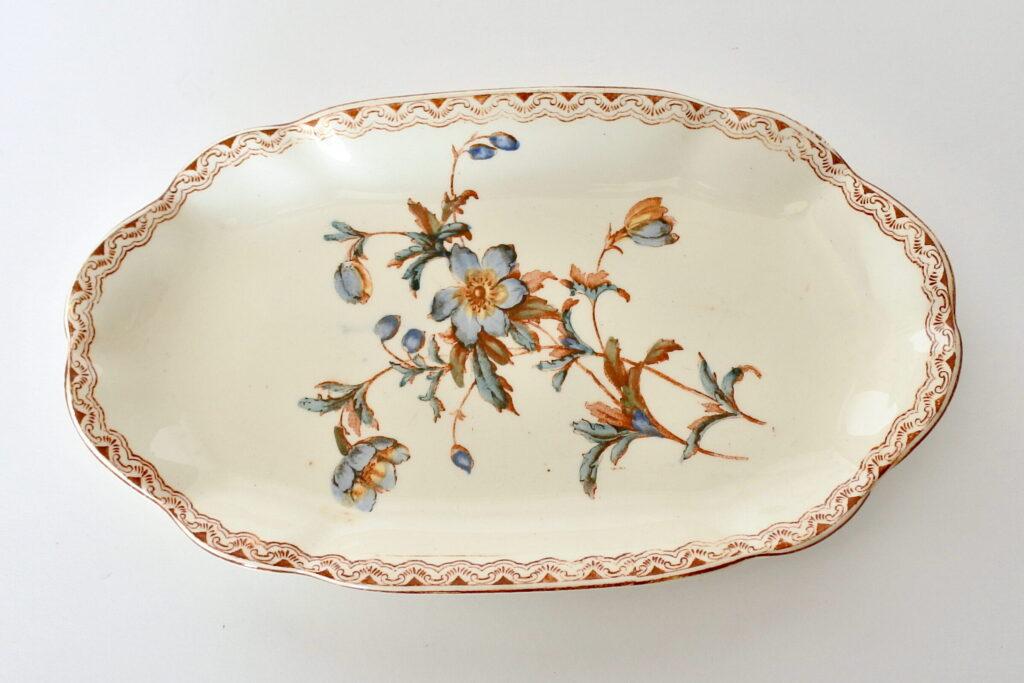Raviera in ceramica di Salins decorata con greca e rami di fiori blu e marroni
