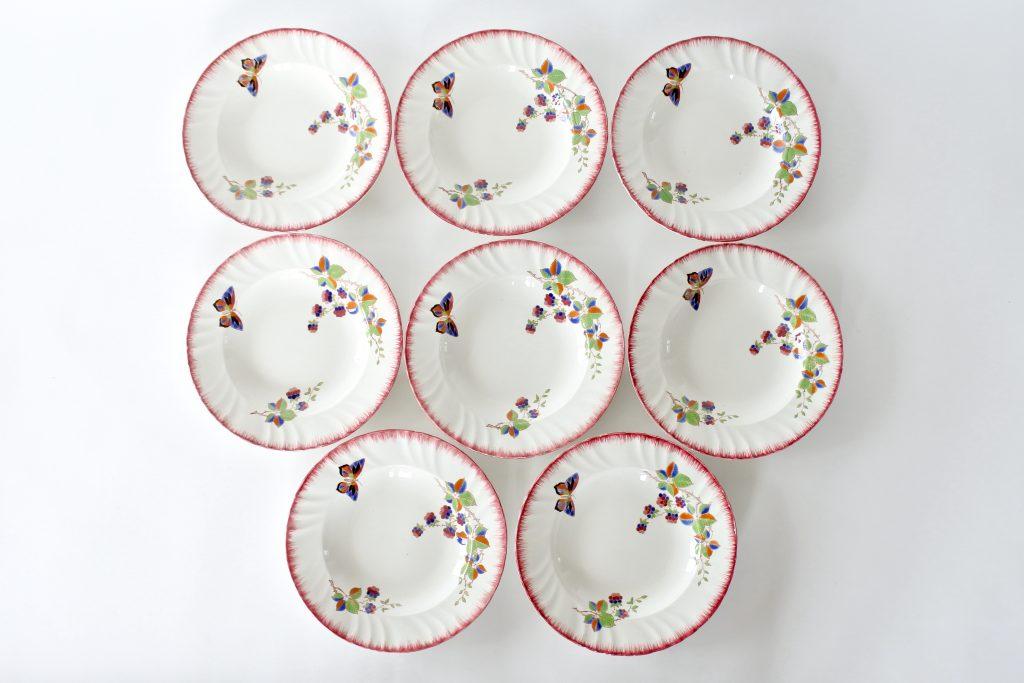 8 piatti in ceramica di Longwy decorati con farfalla e frutti di rovo