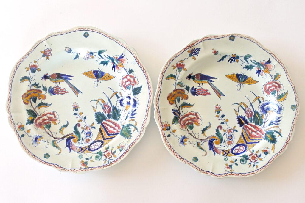 Coppia di piatti fondi in ceramica di Gien con cornucopia farfalla fiori ed uccello