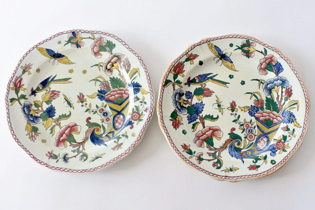 Coppia di piatti piani in ceramica di Gien con cornucopia farfalla fiori ed uccello
