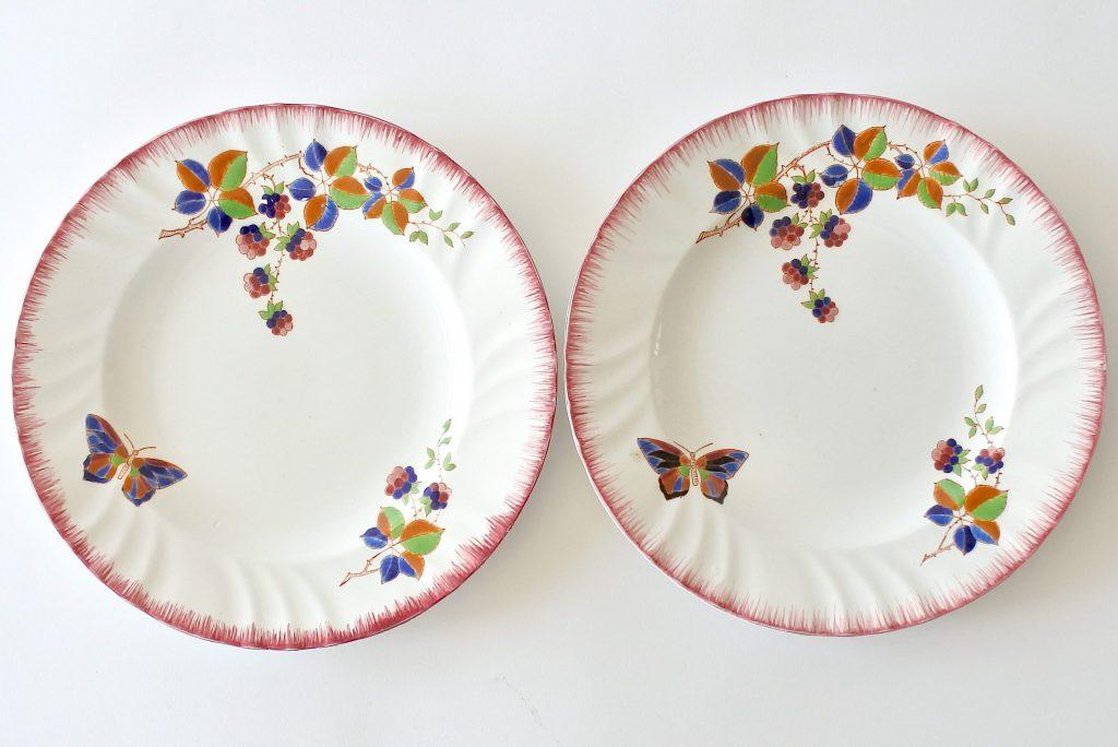 Coppia di piatti piani in ceramica di Longwy con farfalla e rami di more