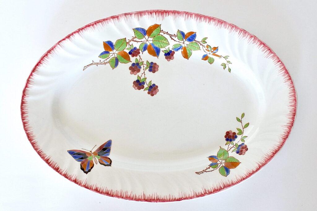 Piatto ovale in ceramica di Longwy decorato con frutti di rovo e farfalla