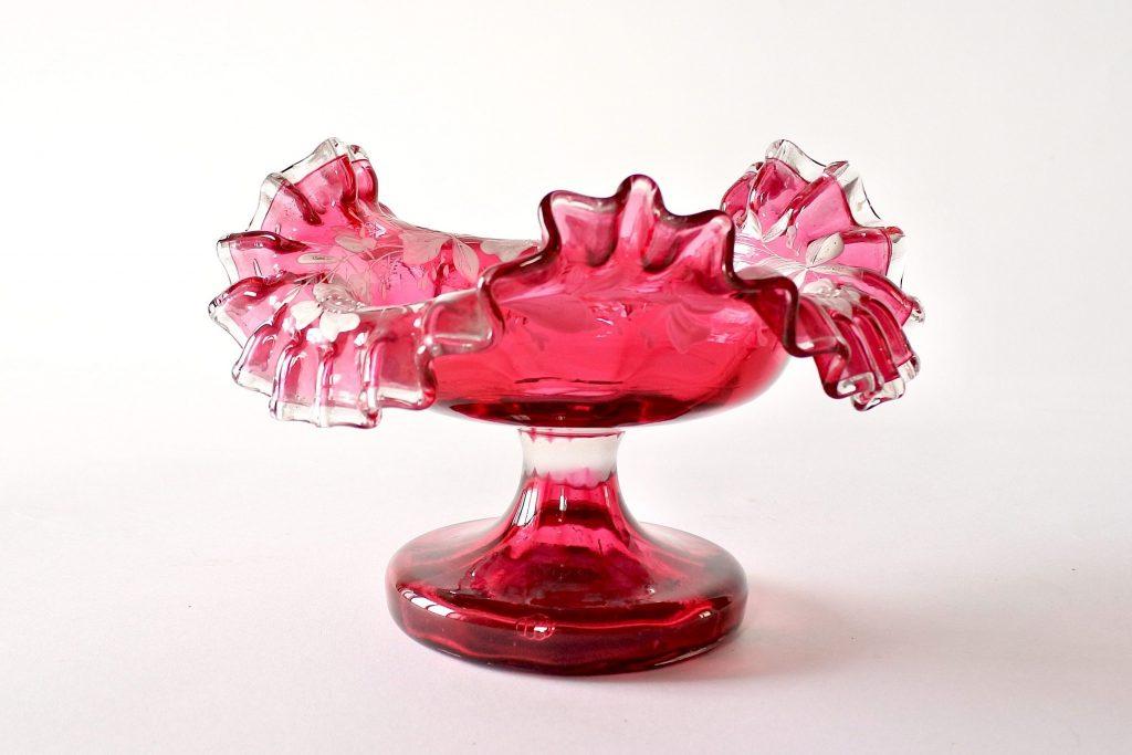 Alzatina in vetro soffiato rosso con bordo dentellato e fiori smaltati bianchi